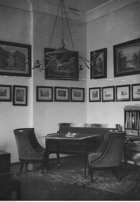 Gabinet hrabiny Magdaleny z Dzieduszyckich Morskiej. Widoczny stolik, sofa, dwa fotele, po prawej stronie fragment sekretarzyka. Obrazy przedstawiają widoki Zarzecza i różnych dworów.